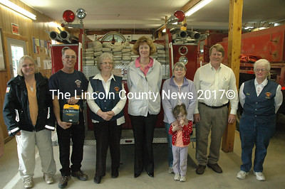 Members of the Somerville Fire Department, joined by CMP officials, after receiving an AED donated by the power company. Pictured, left to right: Selectman Martha Staples, Fire Chief Mike Dostie, Town Clerk Ernestine Peaslee, CMP President Sara Burns, Peggy Dostie with future firefighter Bianca Dostie, CMP Project Manager Bill Sawyer and Elaine Porter. (Samuel J. Baldwin photo)