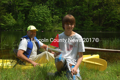 Seventh-grader Camden Golden holds his boat - the only vessel to survive the perilous journey upright. Jay Glendinning (left) oversaw the boatbuilding as part of the school's artists-in-residence program. (J.W. Oliver photo)