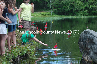 A South Bristol School student launches her boat on Thompson Pond June 10. (J.W. Oliver photo)