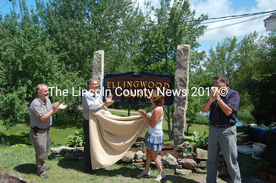 From left, Gary Howard, Rob Howard and Terri Wiseman, the grandchildren of Gary and Dot Ellingwood, applaud after unveiling the Ellingwood Park sign. Chad Hanna, the chairman of the Bristol Board of Selectmen, joins at right. (J.W. Oliver photo)