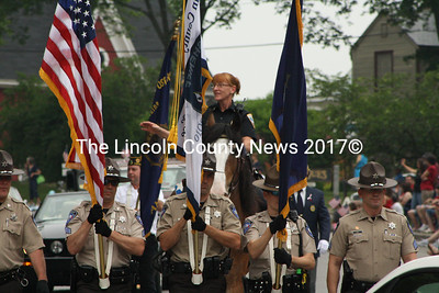 As the color guard from Two Bridges Regional Jail provides cover,Wiscasset Police Sgt. Kathy Williams surveys the crowd while riding atop Rowan, a retired Boston police horse, during the annual Fourth of July parade in Wiscasset. (Matthew Stilphen photo)
