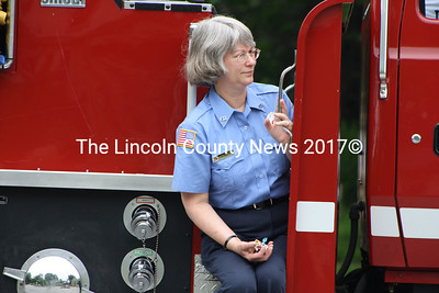 Candy at the ready, Beth Whitney of the Alna Fire Department looks for an opening in the crowd during the Fourth of July parade in Wiscasset. (Matthew Stilphen photo)