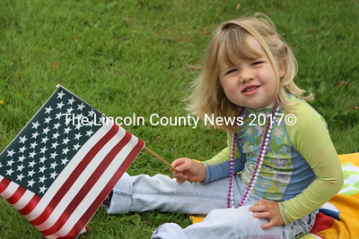 Siena Scardino of Wiscasset salutes the parade participants during the annual Fourth of July parade in Wiscasset. In addition to Scardino, hundreds more lined Main Street to celebrate the nations birthday. (Matthew Stilphen photo)