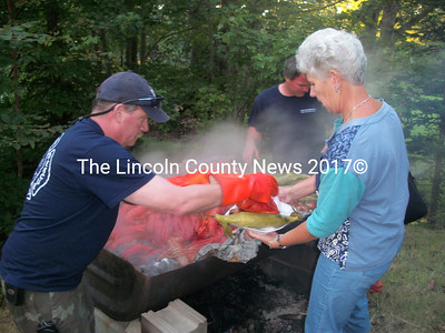 South Bristol Assistant Chief Mark Carrotchers serves up a lobster to Lincoln County  Commissioner Lynn Gilley Orne, Aug. 17. (A. Brodsky photo)