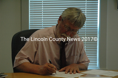 New Waldoboro Town Manager John Spear signs his contract with the town on Aug. 19. (Samuel J. Baldwin photo)