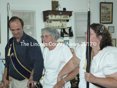 Marian Griffin, center, is escorted to the altar by Rick Grotton and Sharon Manley to receive recognition for her 75 years of Grange membership. (Laurie McBurnie photo)