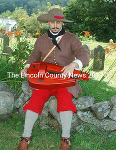 Visitors to the 17th Century Encampment at Colonial Pemaquid were greeted by  Mathieu Lavoie, from Montreal, dressed as a 1690s French soldier, sitting in a shady spot near the old cemetery and playing a hurdy-gurdy. (E. Busby photo)