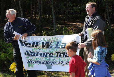 Neil Lash is all smiles as his son and Medomak athletic director Matt Lash presents him with the banner naming the new trail system at Medomak Valley High School after him.
