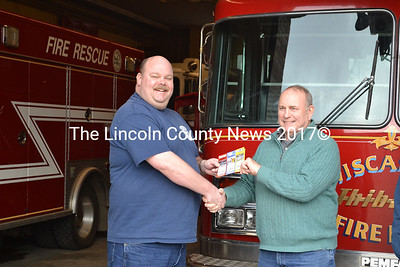 Wiscasset Fire Chief Rob Bickford hands Major Glenn Plyler (Ret.) tickets to the Sprint Cup's Kobalt Tools 400 in Las Vegas. Plyler was the grand prize winner of the Wiscasset Fire Dept.'s annual raffle. (A. Brodsky photo)