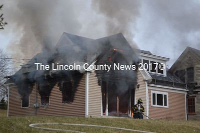 A Wiscasset firefighter attempts to put out a house fire on West Alna Road in Wiscasset Dec. 30. (A. Brodsky photo)
