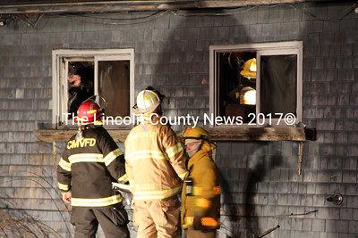 Firefighters watch through a window while their compatriots wind up response efforts inside the rental home at 90 Rockland Rd. Dec. 28. (Elizabeth Simonds photo)