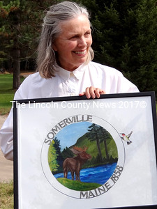 Artist Claudia Fujinaga holds the original oil painting of her design for Somerville's new town seal. Elaine Porter is making a sign for the new town office that will inculde Fujinaga's artwork. (Shlomit Auciello photo)