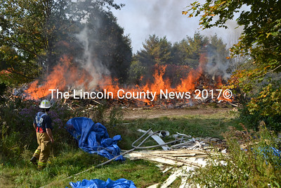 Edgecomb Fire Chief Roy Potter keeps an eye on a controlled burn of an unsafe building Oct. 6. (D. Lobkowicz photo)