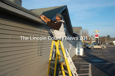 Hilltop Stop owner Gary Gravel hangs Christmas lights at the Damariscotta convenience store. (J.W. Oliver photo)