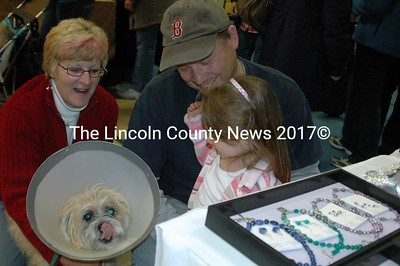 """Jo-Ann Freburger who designs """"For the Luv of It"""" handcrafted jewelry and her dog Winston, show 3 year old Claire Libby and her dad Scott some necklaces. Claire and Scott are from New Harbor."""