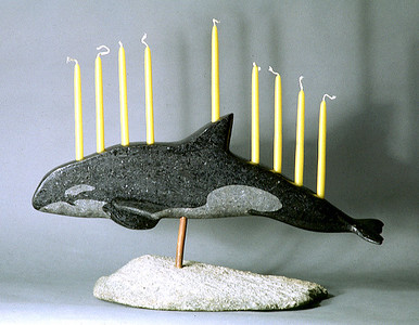 While strict Jewish tradition calls for all candles on a Chanukah menorah except the shamash (used to light the others) be on the same level, artisitc license is often taken. This granite menorah is by Joe Auciello of Rockland. (Shlomit Auciello photo)