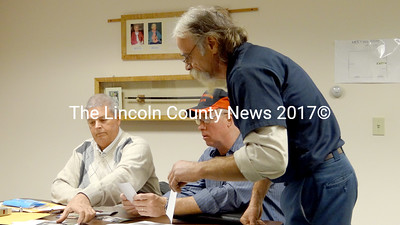 Jefferson Code Enforcement Officer Stanley Waltz (left) and Road Commissioner Alan Johnston review pictures sumblitted by landowner Pierre Girard (right) who has done work on his Musquash Pond property without proper permits. (Shlomit Auciello photo)
