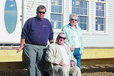 John (center) and Lynn Ring, with friend and builder Nathan Powell, in front of Rings new home at 16 Oceanside Road in 2011.A fire destroyed the Rings' previous home March 9, 2011. On Dec. 9 another fire damaged the garage and resulted in the death of Lynn Ring. (LCN file photo)