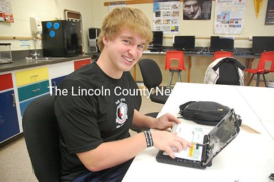 Lincoln Academy sophomore and Student Technology Team member Wally Morris repairs a loose video cable on a school-issued netbook. (J.W. Oliver photo)