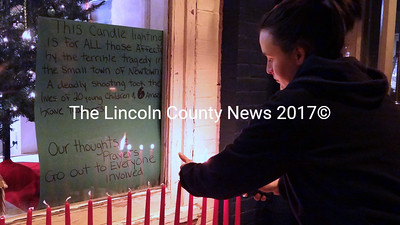 Waldoboro business owner Tawsha Hisler lights 26 red tapers to honor victims of the Dec. 14 mass shooting in Newtown, Conn. (Shlomit Auciello photo)