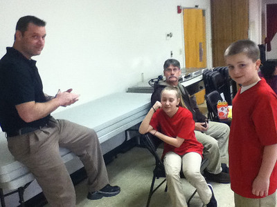 Grand Master Edward Hall, owner of Halls Olympic Martial Arts Studio in Bath with students Madison Nelson, of West Bath, and Wiscasset Middle School sixth grader and black belt in TaeKwanDo, Hunter Raedel relaxing between video scenes. (K. Fletcher photo)