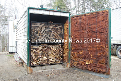 Frick & Frack feeds waste wood into a furnace to heat this kiln to about 275 degrees Fahrenheit. The kiln removes about 1500 pounds of water from a single cord of wood. (J.W. Oliver photo)