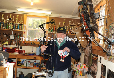 David Abbott holds up his winning bow and the patches and ribbons he won at the National Field Archery Association's sanctioned Maine Indoor Archery championships March 25. Abbott set two Masters records and won two state titles in the tournament. The walls of Abbott's shop are lined with numerous trophies and awards he has won over the past half century. (Paula Roberts photo)