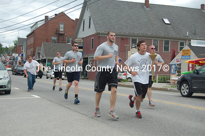 Special Olympics athlete Mat Poland carries the torch on Main Street, Damariscotta, flanked by Damariscotta Police officers Caleb Brown (left) and Jason Warlick. (J.W. Oliver photo)