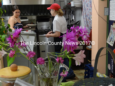 In the kitchen at Mazies Restaurant, owner Miranda Pease (left) presents finishes preparing a plate of hot dogs and beans for waitress Denise Wagner to bring to a customer. (Shlomit Auciello photo)