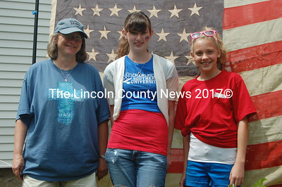 From left to right are Kathleen Maclachlan, pastor of the Bremen Union Church; Becca Tutton, of Front Royal, Va.; and Gabbi Miles, of Orford, N.H. staning before an American Flag dating to the late 19th or early 20th century. Tutton and Miles said they attend the church when they visit their grandparents in Maine. (J.W. Oliver photo)