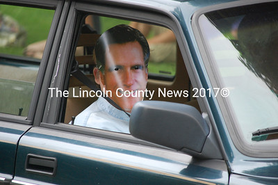 """Republican presidential candidate Mitt Romney smiles at the crowd from the window of a station wagon. A sign on the front of the car claims """"Mitt Vacations in Round Pond."""" (J.W. Oliver photo)"""