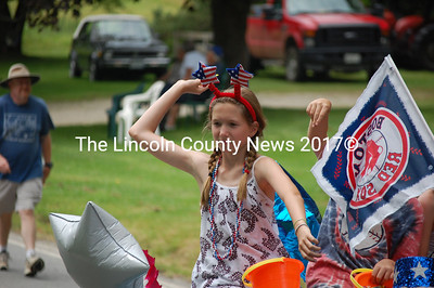 A girl in a patriotic headband throws candy to the roadside audience. (J.W. Oliver photo)