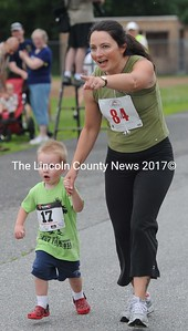 Sarah Hinners runs the last 50 yards with three year old Jasper Pasko in the half mile fun run at the Strawberry Shortcake Shuffle on July 7..