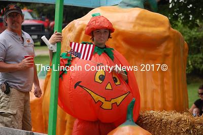 A kid in a pumpkin costume waves an American Flag on the Damariscotta Pumpkinfest float. (J.W. Oliver photo)
