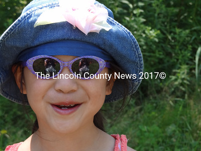 Olivia Hardina, 9, of Nobleboro said her favorite thing to eat from a farm is pork chops. On Open Farm Day at County Fair Farm in Jefferson, she enjoyed watching a flock of hens scrabble around for feed. (Shlomit Auciello photo)