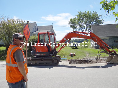 Michael Lamarre, of John York Enterprises, flags traffic during a waterline repair on Bayview Road in Nobleboro, July 20. Originally, municipal water was piped by gravity feed, from Damariscotta Lake to houses in Damaraiscotta Mills. Between six and eight homes still use that supply. The hole has been filled in, and after the earth settles the road will be patched with pavement, according to John York, who also serves as Nobleboro's road commisioner. (Shlomit Auciello photo)