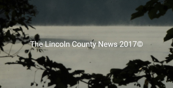 A lone paddler makes its way through fog on Damariscotta Lake Wednesday morning.