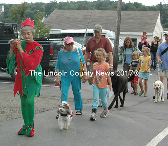 """The Pied Piper, in the person of Linda Brunner plays """"How much is that Doggie in the Window?""""  on the piccolo led the Damariscotta-Newcastle Rotary Canine Capers Grande Parade.  (E. Busby photo)"""