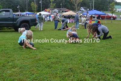 Youngsters earnestly search for scattered pennies during a penny hunt at the Jefferson Community Day. (Sherwood Olin photo)