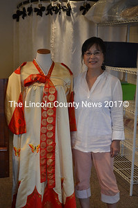 Insook Hudson is completing the finishing touches on her new location in the Damariscotta Center building. She stands with her own garment, which she wore regularly as a young woman growing up in South Korea. (K. Fletcher photo)