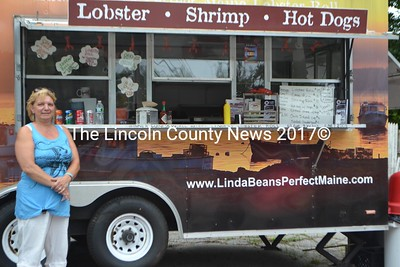 Jenny DiSanto stands in front of the new lunch truck in Wiscasset that opened July 14, serving lobster rolls, shrimp rolls, hot dogs, hamburgers, and Orr's Island Seafood Chowder. Warren Hewes owns the business, and leases the truck from Linda Bean. (Honora Perkins photo)