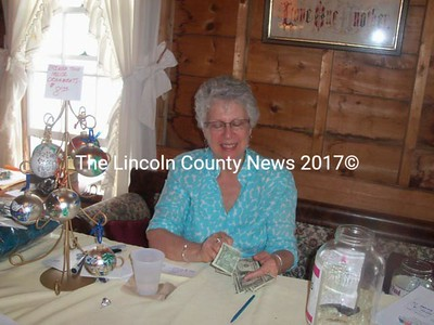 Katie Varian of the Bremen Town House Committee tallies the results of the silect auction at Bremen's Chocolate Sunday Aug. 5. The money raised will go toward restoring the Bremen Town House. (Honora Perkins photo)