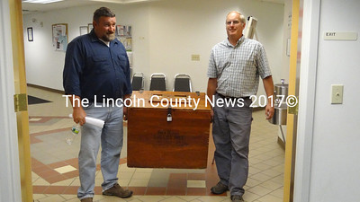 From left, Waldoboro Public Works Director John Daigle and Assessor's Agent and General Assistance Administrator Darryl McKenney carry ballots from the Public Safety garage, where voting took place Sept. 11. B. After more than four hours of tabulation, the count showed that voters had given approval to all the ballot questions. (Shlomit Auciello photo)