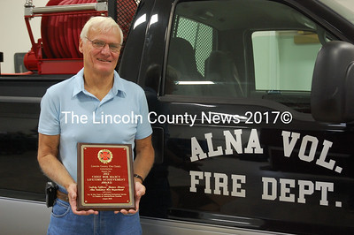 James Bruce, a recent recipient of the Lincoln County Fire Chiefs Assn. Chief Bob Maxcy Lifetime Achievement Award, holds the plaque recognizing him for his 31 years of service to the Alna Volunteer Fire Department. (J.W. Oliver photo)