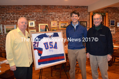 Bobby Whear (left) donated a replica 1980 USA Olympic Hockey Jersey signed by 1980 team captain Mike Eruzione as a raffle prize to benefit the installation of the DRA Skating Rink lights installed by Mid-Coast Energy Systems. With Whear is DRA Executive Director Steve Hufnagel and DRA Board Member Matt Filler. (Kim Fletcher photo)