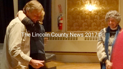 Lincoln County Community Theater and Orchestra volunteer Jim Buckingham, left, receives a congratulatory hug from Nancy Durgin after receiving an American Association of Community Theaters Spotlight Award. Watching, right, is Suzanne Rankin. (Shlomit Auciello photo)