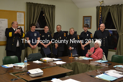 Wiscasset Fire Chief Rob Bickford (left) and Jackie Lowell (seated) applaud firefighters (from left) Spencer Bailey, Nick Grover, Bobby Meisimer, Sam Schmall, Steven Smith and Tim Weatherbee, (not present Cody Haggett, Nick Merry, and James Pray) who were honored on Jan. 22.  (D. Lobkowicz photo)