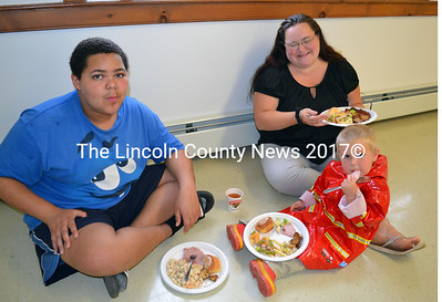 With the tables full at Alna's Annual Ham and Bean Supper Isiah Seigars, Tammy Seigars and Gabrielle Ganun find a spot on the floor to eat their dinner. (Kathy Onorato photo)