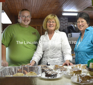 Ashton Harvey and Jeanette Wheeler, both of Waldoboro, and Kerry Weber, of Bremen, stand with some of the sweets and treats for sale at the Bremen Country Fair. Wheeler and Weber both made food to sell, and all three lent helping hands at the event. (D. Lobkowicz photo)