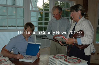 """Barton Seaver signs a copy of his book """"For Cod and Country"""" for Tom and Wendy Eichler of Wiscasset. The Maine Coast Book Shop sponsored a talk and tasting featuring Seaver, an author, chef and sustainable food expert at The 1812 Farm in Bristol Oct. 3. (J.W. Oliver photo)"""